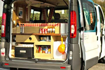The backdoor kitchen/galley unit  in a travel van up and close.