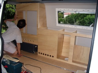 installing homemade furniture in a camper van conversio