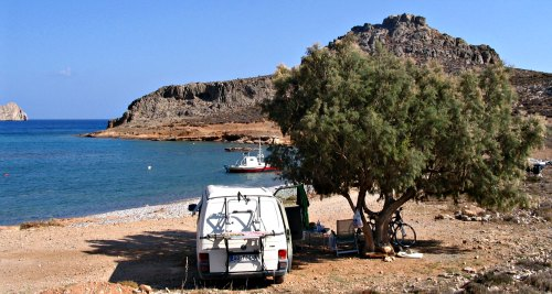 A Volkswagen camper van  wild camping on a lonely beach in southern Crete, Greece.