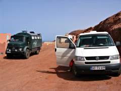 Volkswagen camper van and a 4x4 Mercedes Unimog conversion on the south Atlantic beach in Morocco.