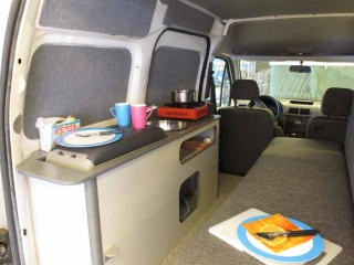 The kitchen and sofa/bed in a mini camper van conversion.