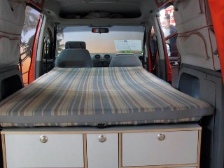 A cozy twin bed in a mini camper van conversion