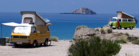 Two generations of Volkswagen Westfalia camper vans wild  camping on a  beach in Greece
