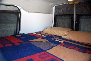 The twin bed in a mini camper with storage room below the bed. So much better than a tent!
